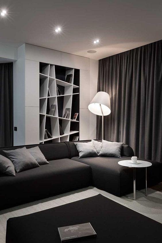 a contemporary black and white living room with a built in geometric shelf, a sectional sofa and a black ottoman