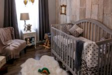 a cool rustic nursery with a reclaimed wood wall, a large grey crib, a fluffy rug, dark curtains and a vintage chandelier