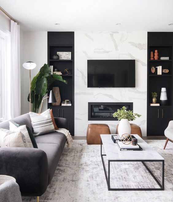 a cozy Scandinavian living room with a marble wall, a built in fireplace and chic furniture plus potted greenery