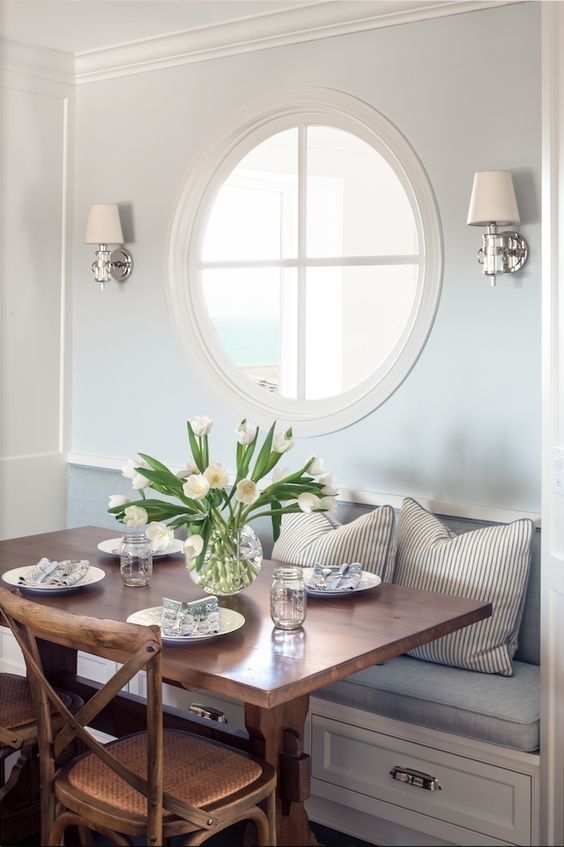 a cozy dining nook with a porthole window and wall lamps looks very refined and very chic