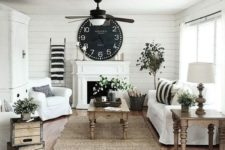 a cozy farmhouse living room in black and white is warmed up with natural wooden furniture and potted greenery