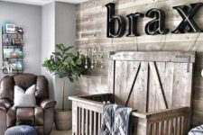 a cozy farmhouse nursery, a reclaimed wood wall and a matching crib, a name on the wall, a leather chair and a lamp fan