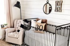 a cozy nursery with a shiplap wall, a black metal crib, a printed rug, a blush chair and blush curtains plus touches of black for drama