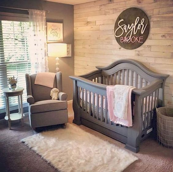 a cozy small farmhouse space with a reclaimed wooden wall, a grey crib and chair, a fluffy rug and shades on the window