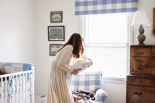 a cute famrhouse nursery with lot sof blue plaid, a stained dresser, a neutral rug and a white vintage crib