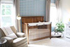 a cute farmhouse nursery with a blue plaid wall, a stained crib, vintage furniture, grey curtains and a creamy rug