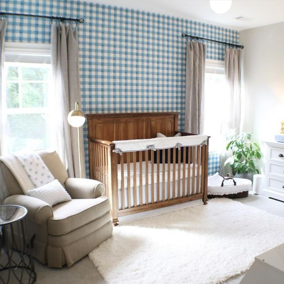 a cute farmhouse nursery with a blue plaid wall, a stained crib, vintage furniture, grey curtains and a creamy rug