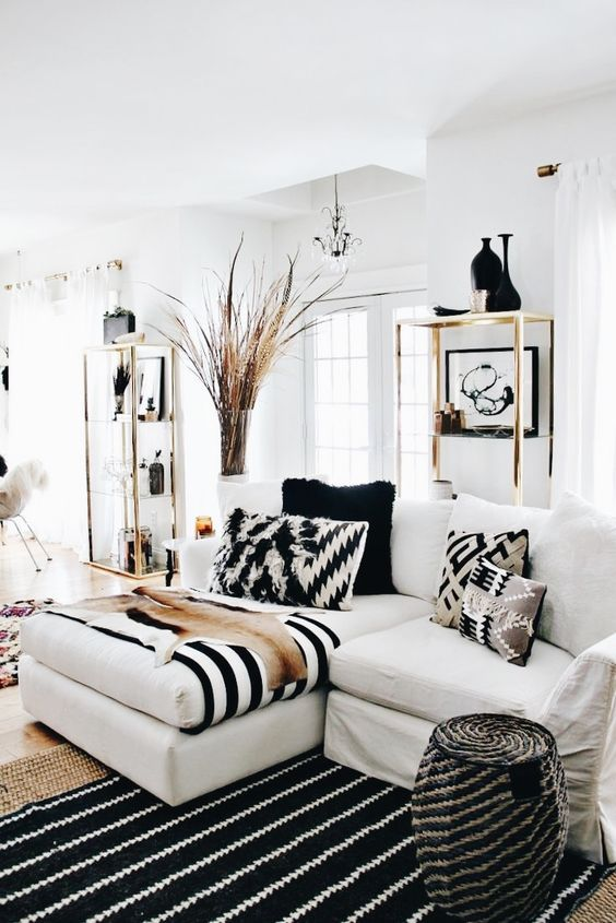 a fantastic black and white living room with stripes and chevrons, gilded touches for a glam feel and a dried herb arrangement