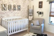 a farmhouse nursery with a whitewashed brick wall, an animal skin rug, grey furniture and a vintage chandelier
