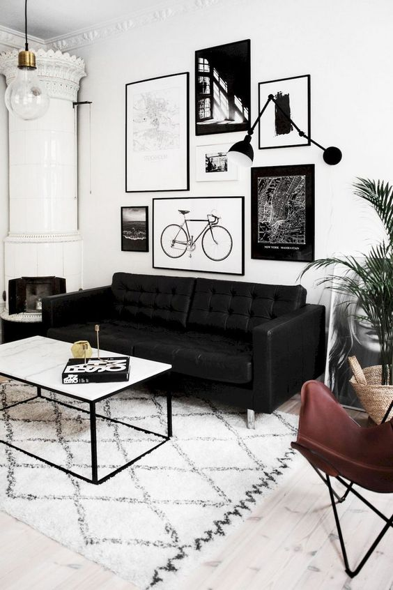 a gorgeous Scandinavian living room with a gallery wall, a vintage stove, a black sofa and some chic furniture plus greenery