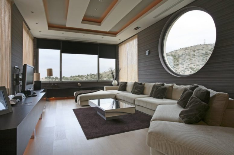 a gorgeous contemporary living room with a large round window and a panoramic window with shades to maximize the views