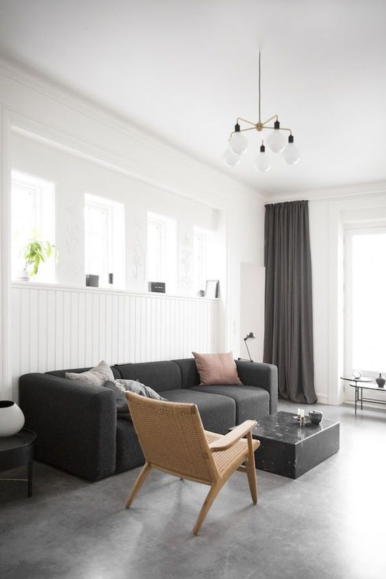 a laconic monochromatic living room with white beadboard walls, black furniture and textiles and a stone floor