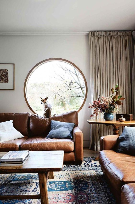 a large round window with wooden framing perfectly matches the chic living room and its color scheme