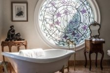 a luxurious bathroom with a mosaic round window, a clawfoot bathtub and refined furniture here and there