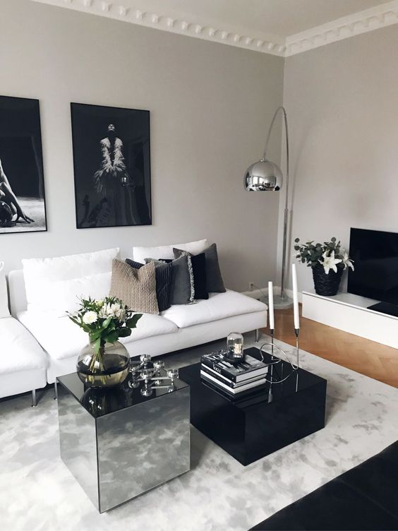a luxurious black and white living roo with stylish contemporary furniture, black and mirro coffee tables and a dark gallery wall