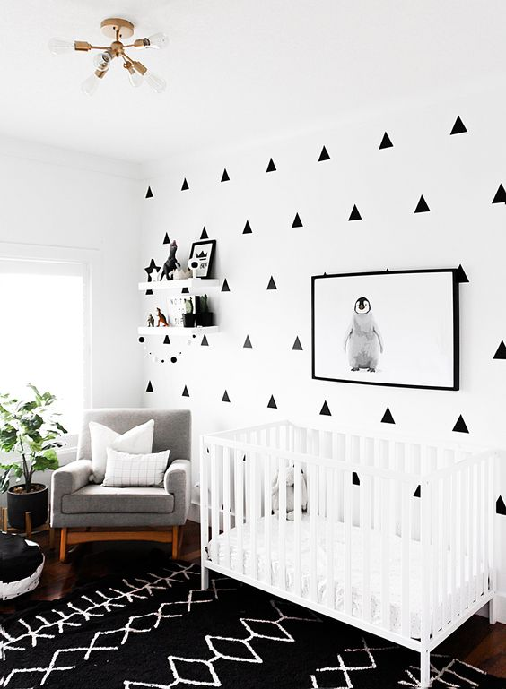 a modern black and white nursery with a patterned wall, a printed rug, a white crib and a penguin artwork