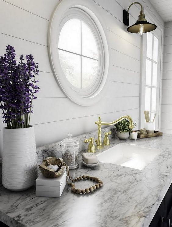 a modern farmhouse kitchen with a marble countertop and a porthole window plus a usual one next to it