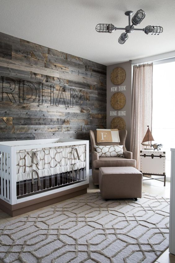 a modern farmhouse nursery with a reclaimed wooden wall, a taupe chair and footrest, a modern crib with acryl and a printed rug