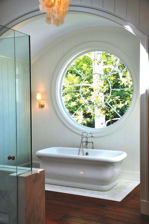 a modern farmhouse with a large porthole window next to the tub to fill the space with natural light