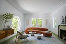 a modern luxurious living room with a large round window, which allows amazing views, and a usual one