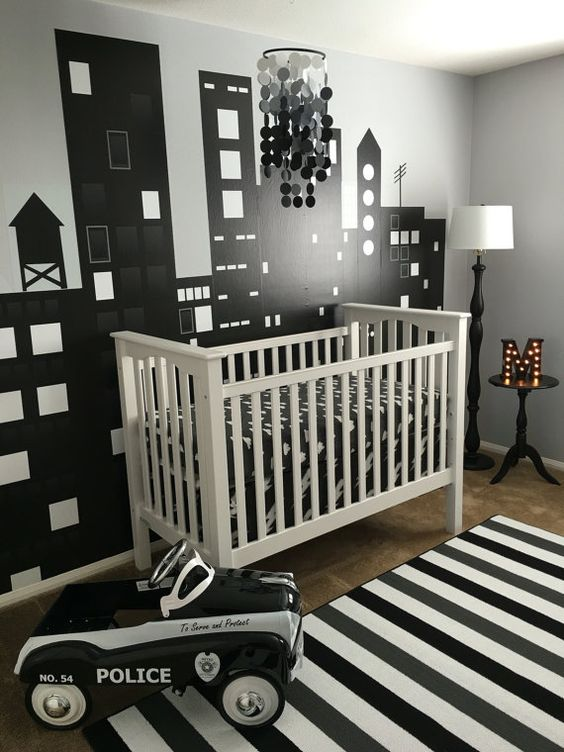 a modern monochromatic nursery with a white crib, a striped rug, an ombre sequin chandelier and a marquee monogram