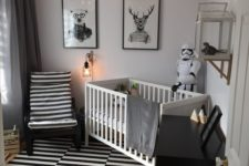 a monochromatic nursery with a striped rug and chair, a black dresser, a white crib and bulbs attached to the ceiling