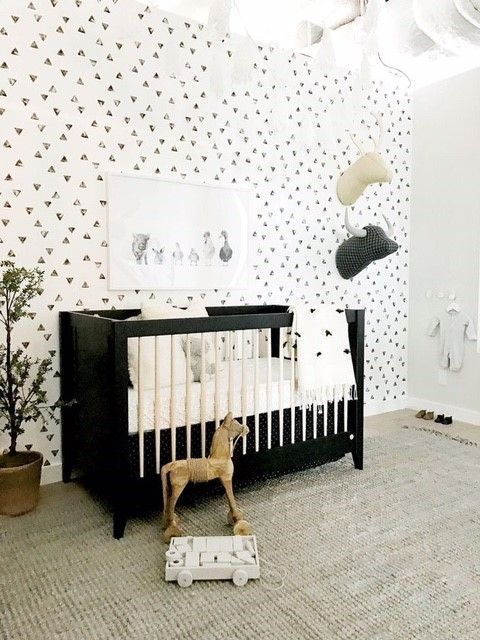 a monochromatic space with a printed wall, a black crib, toy heads on the wall and a large rug