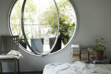a neutral and airy bedroom done with a round pivot window, which allows fresh air in easily