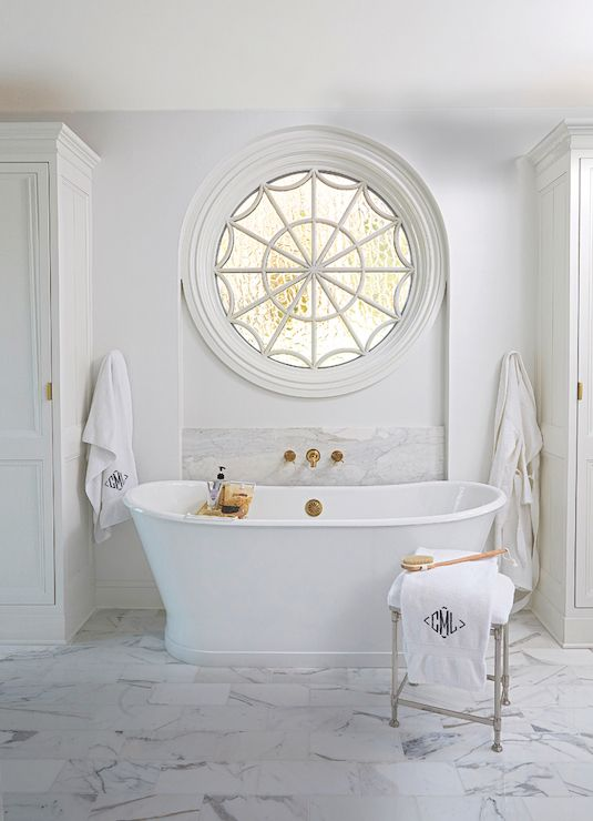 a neutral farmhouse bathroom done with marble tiles, a chic tub and a porthole window next to the tub