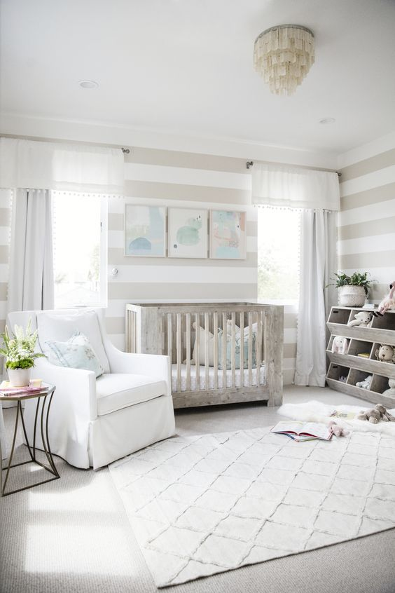 a neutral farmhouse nursery with a whitewashed crib, a unique chandelier, a printed rug and stripes on the walls