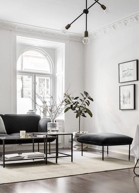 a refined Parisian-inspired living room with chic black furniture, a black chandelier and a gallery wall