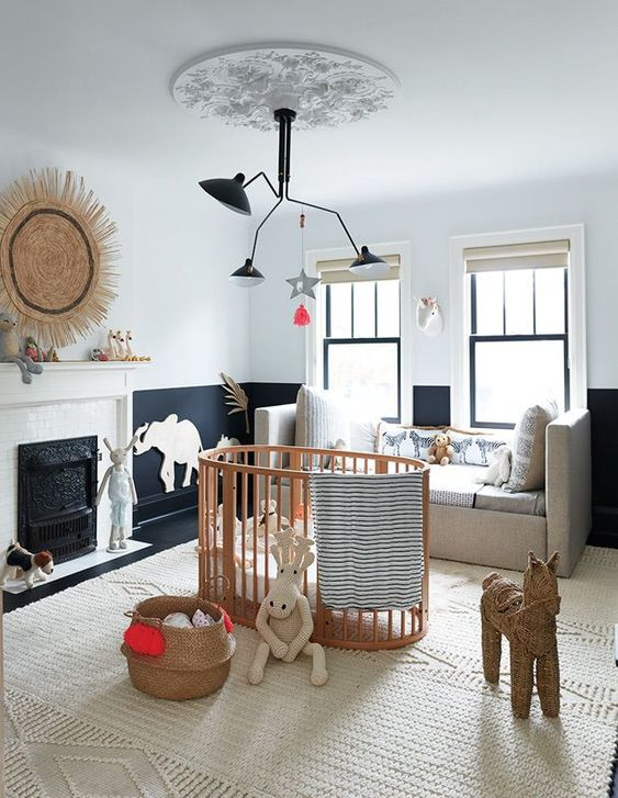 a refined black and white nursery with a neutral rug, sofa and a woodne crib plus baskets