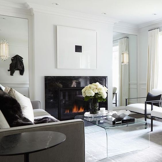 a refined contemporary living room with a sleek black fireplace, a sheer acrylic table and some black touches for drama