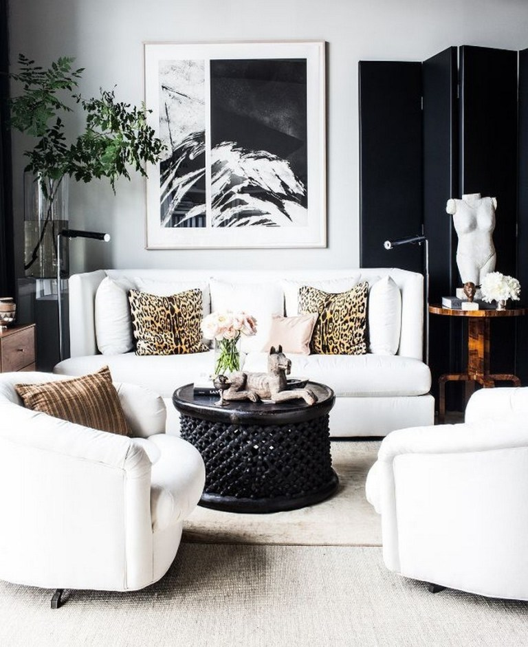 a refined living room with a white sofa, a large statement artwork, elegant furniture and a folding screen to accent the space