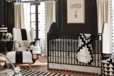 a refined nursery with lots of prints, a crystal chandelier, a black and white crib and gorgeous furniture