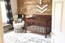 a rustic nursery with a printed rug, a stained crib, a reclaimed wall and some touches of prints