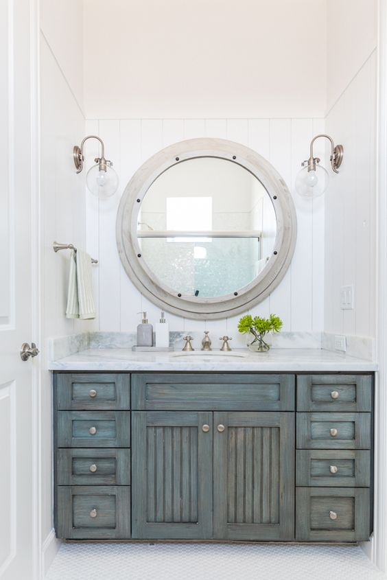 a shabby chic coastal bathroom with an ged wood vanity and a large porthole window to the shower