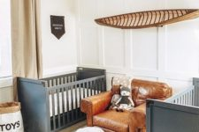 a shared farmhouse nursery with grey cribs, a leather chair, an antler chandelier and an animal skin rug