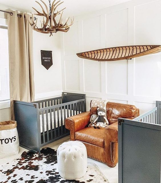 a shared farmhouse nursery with grey cribs, a leather chair, an antler chandelier and an animal skin rug