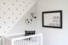 a simple contemporary nursery with a printed rug and wall, a grpahic artwork and a geometric black lamp