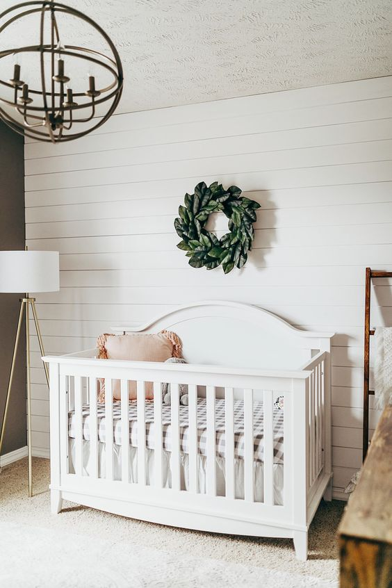 a simple nursery done with a white shiplap wall, a white vintage crib, a sphere chandelier and a faux greenery wreath