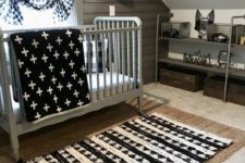 a small attic nursery with a jute rug, a printed one, a grey vintage crib, prints and a reclaimed wooden wall