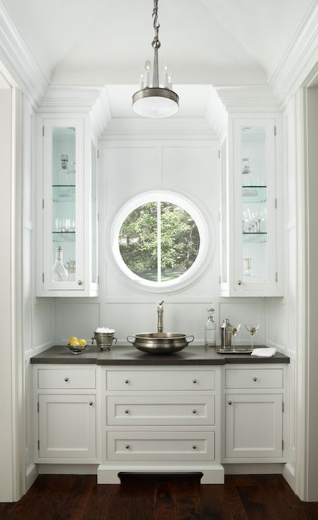 a small home bar with traditional white cabinets and a small porthole window to make the space unique