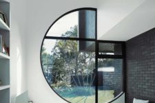a small minimalist living room in white with a large porthole window partly integrated into the wall