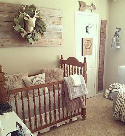 a small vintage farmhouse nursery with a reclaimed wood artwork, a vintage crib, cozy rugs and furniture