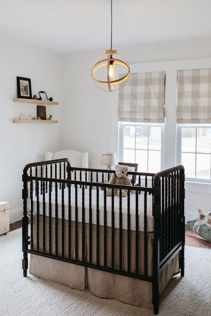 a small yet cozy nursery with plaid Roman shades, a vintage black crib, a sphere pendant lamp and floating shelves