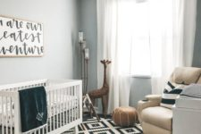 a stylish black and white nursery with a neutral leather chair and an ottoman to add warming touches