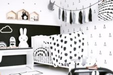a stylish black and white nursery with monochromatic furniture, a tassel garland, a white crib and lots of prints