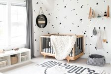 a stylish black and white space with a printed rug, star print walls, a contemporary crib and a black lampshade