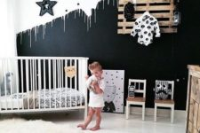 a stylish black and white space with an accent wall, a pallet clothes rack, a white crib and some more monochromatic touches